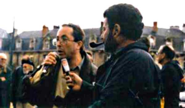 Gilles Durou (esquerra) entrevistat per Gilbert, de «La Clé des Ondes» en una trobada pels sense-papers (2002)