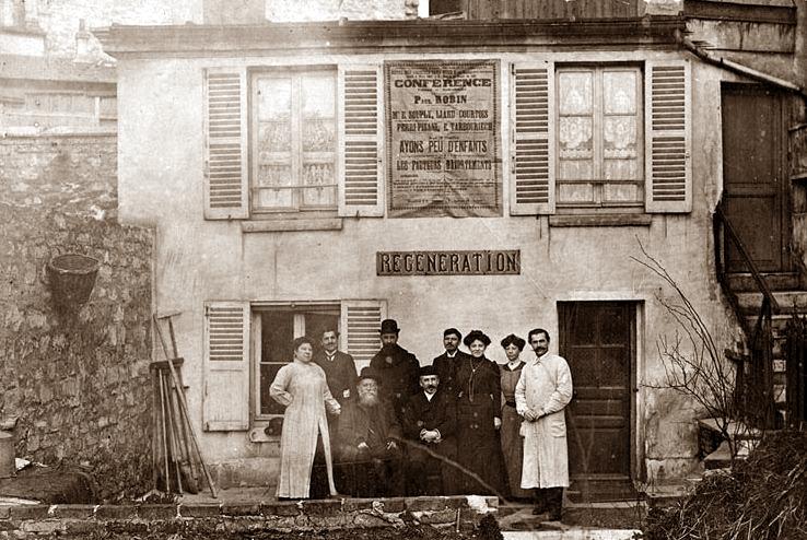 """Locals de """"Régéneration"""", al número 27 del carrer de la Duée de Paris (març de 1907). Asseguts: Paul Robin (a l'esquerra) i Fernand Mascaux, fundador de la «Ligue Néo-malthusienne Belgue» (a la dreta). Drets, d'esquerra a dreta: Eugénie de Bast, Albert Gros, Gabriel Giroul, Fernández, la companya de Fernández, Emilia Souply i Eugène Humbert"""
