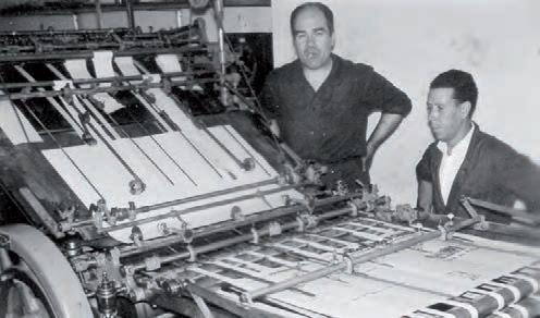 Tomás Marcellán Martínez (tipògraf) i Bautista Agustí Pérez (mecànic) durant el reglatge de la màquina «Lambert» (1956)