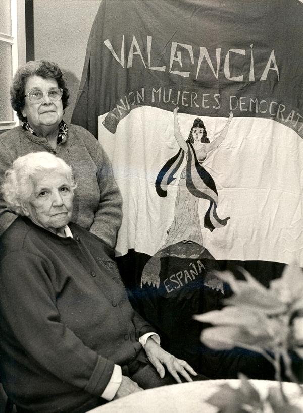 Isabel Mesa Delgado (asseguda) i Angustias Lara amb la bandera republicana de la Unión de Mujeres Demócratas que cosiren en 1944