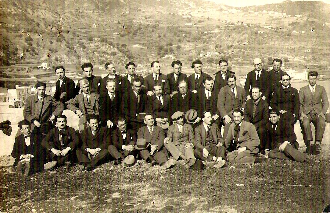 Pasquale Binazzi, assegut en terra amb el capell al genoll, amb un grup de deportats anarquistes a l'arxipèlag de Lipari (1927)