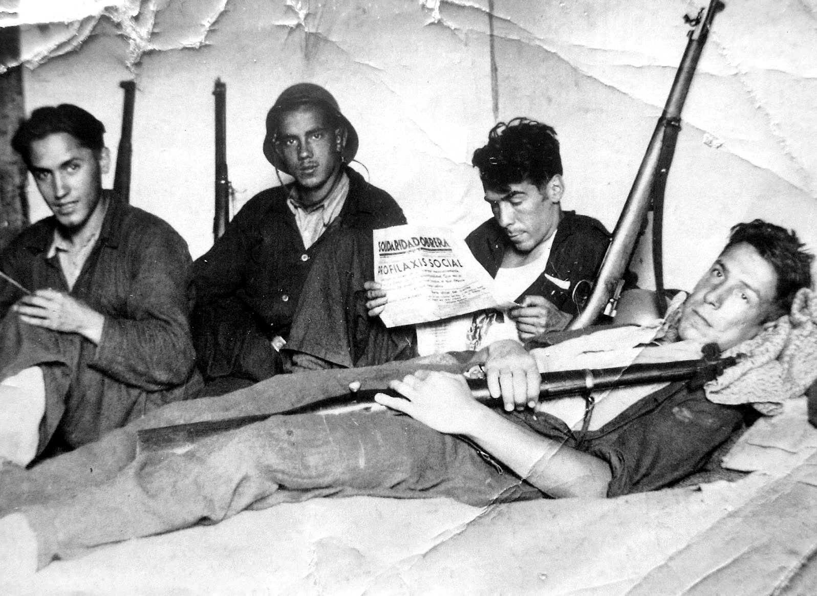 """Alberto Lucarini Macazaga (llegint la """"Soli"""") i altres companys al front"""