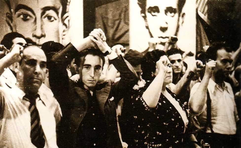 D'esquerra a dreta: Francesc Isgleas, Ramón Liarte, Frederica Montseny i Joaquín Cortes (Teatre Olympia, 21 de juliol de 1936). Tots puny en alt, llevat de Liarte que fa la salutació llibertària